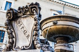 picture of spqr  - Old fountain with the coat of arms of ancient Rome SPQR carved in marble in Rome Italy - JPG