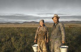 foto of mongolian  - Mongolian Couple Farmers Holding Basin Posing Field Concept - JPG