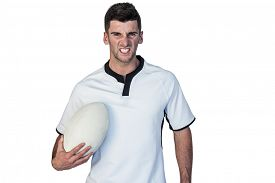 stock photo of irritated  - Portrait of an irritated rugby holding ball over white background - JPG