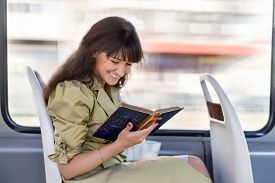 stock photo of tram  - young happy woman reading antique book in the moving tram - JPG