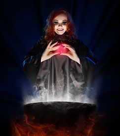 pic of cauldron  - Young witch with potion and cauldron on blue rays background - JPG