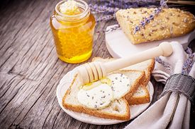 picture of fresh slice bread  - Two pieces of fresh homemade white bread with slices of butter with lavender flowers and honey for breakfast - JPG