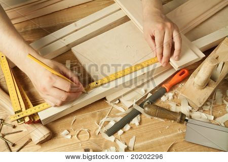 Wooden workshop table with tools. Man's arms measuring.