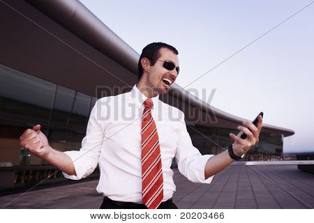 Successful happy businessman in white shirt and sunglasses cheering as having received good news on cell phone with office building in background.