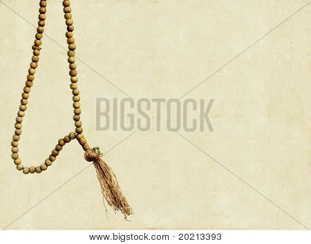 prayer beads on a simple light brown background and plenty of space for text