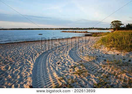 Tracks from a tractor at the sand beach in a calm bay