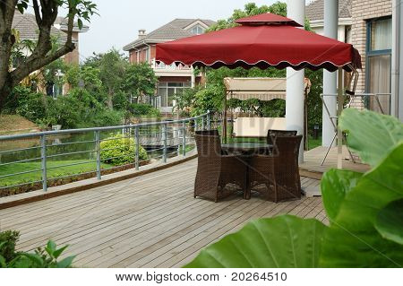 House backyard with table and chairs by a small river.
