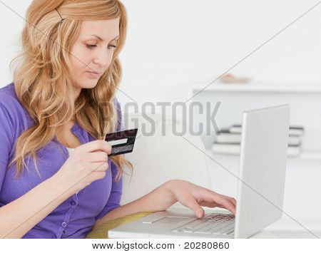 Concentrated woman sitting on a sofa is going to make a payment on the internet in her apartment