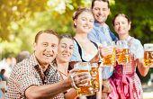In Beer garden - friends in Tracht, Dirndl and Lederhosen drinking a fresh beer in Bavaria, Germany poster