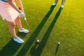 High-angle cropped view of a professional woman player holding the putter golf club, ready to hit th poster