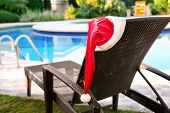 Santa hat on sun lounger near swimming pool at resort. Christmas concept poster
