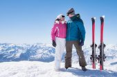 Skier couple standing on snowy mountain top and looking each other. Loving couple with skis with cop poster