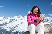 Happy woman using smartphone while sitting on rock with snowy mountains in background. Smiling woman poster