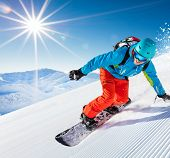 Active man snowboarder riding on slope, snowboarding closeup. poster