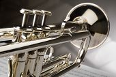 stock photo of musical instruments  - Trumpet on musical notes as background close up - JPG