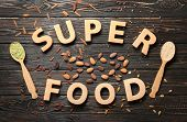 Composition with wooden letters and assortment of superfood products on table, top view poster