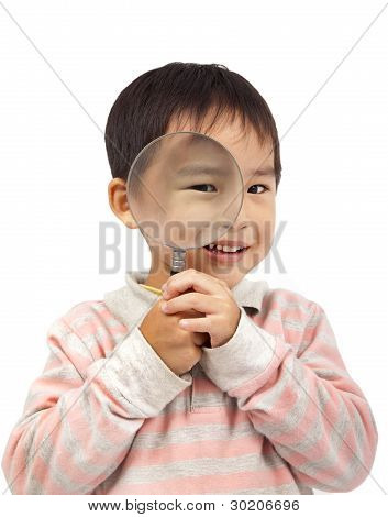 smiling boy holding  the magnifier discover world