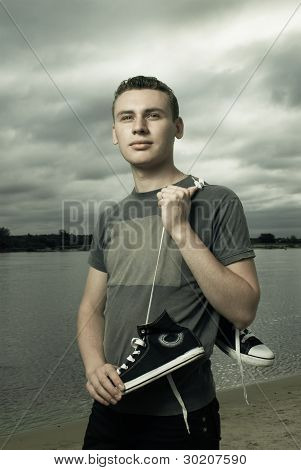 Portrait Of Young Man Standing On The River Bank