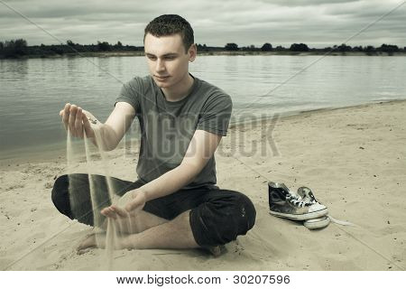 Thoughtful Young Man Sitting On The Beach
