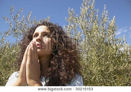Young woman praying outdoors