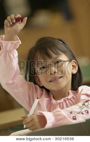 Junge Mädchen heben ihre Hand in Klasse