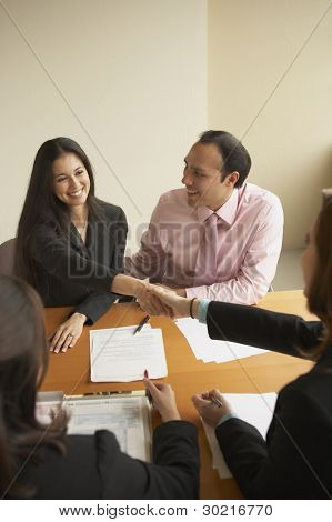 Couple shaking hands with businessman