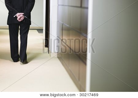 Businessman walking down corridor