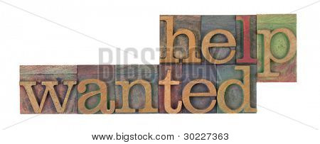help wanted words in vintage wooden letterpress printing blocks, stained by color inks, isolated on white