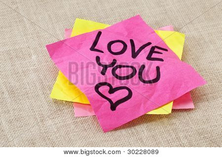 office romance concept - love you text handwritten on red sticky note