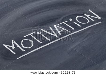 motivation word in white chalk handwriting on blackboard