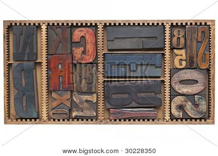 letters and numbers - a variety of vintage letterpress printing blocks  in a small wooden typesetter box with dividers, isolated on white