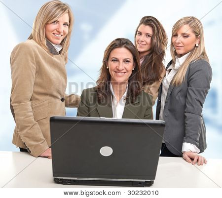 4 women around a desk with computer with happy faces
