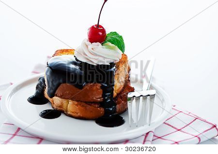 French Toast With Dark Chocolate, White Cream, Red Cherry And A Leaf Mint On A White Background