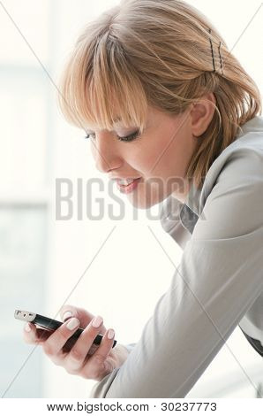 Happy smiling businesswoman looking at smart phone while text messaging
