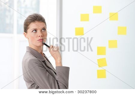 BEautiful young business woman with pensive expression near a question mark sign of post it