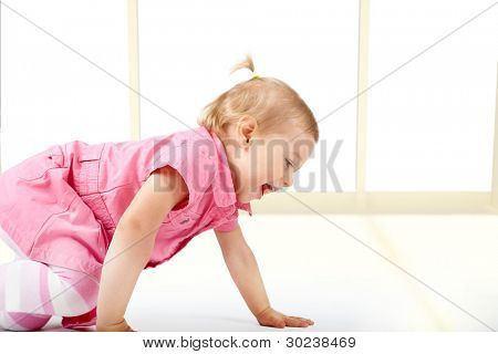 Cute baby girl crawling on the floor in home