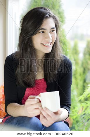 Beautiful Teenage Or Young Woman Drinking Coffee Next To Window