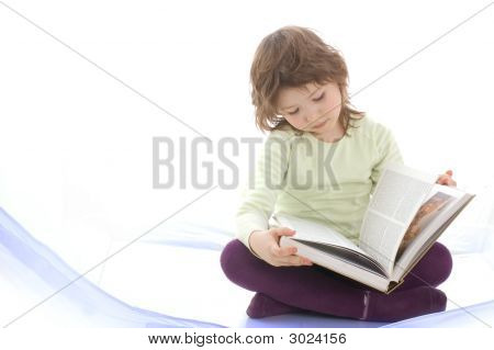 A Young Girl Reading A Book