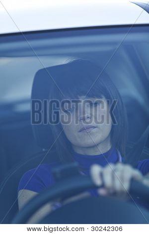 Mujer en riesgo manejando sosteniendo y hablando en su teléfono celular