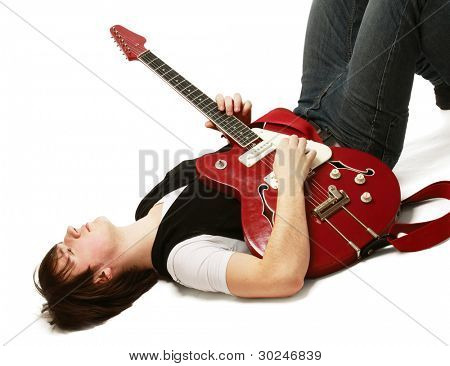 A rock guitarist lying on the floor, isolated on white background