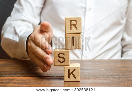poster of A Man Straightens A Segment In An Unstable Tower Of Cubes Labeled Risk. Risk Management, Cost Assess