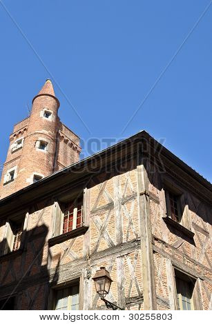Old Architecture Made Of Red Bricks Against A Bright Blus Sky In Toulouse, South Of France