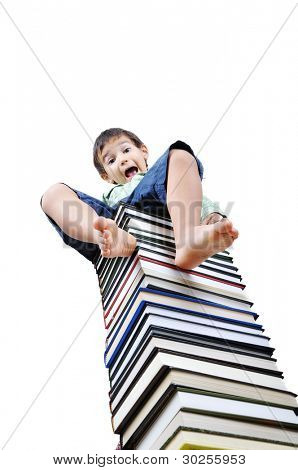 Cute little boy sitting on heap of textbooks
