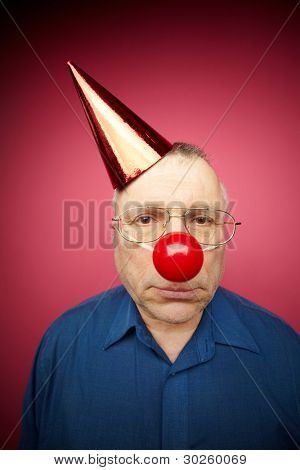 Portrait of unhappy man with a red nose and in a cone cap on fool�s day