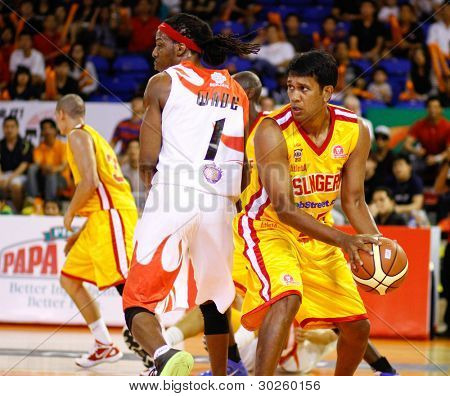 KUALA LUMPUR - FEBRUARY 19: Singapore Slingers' M. Pathman shields the ball from Dragons' Tiras Wade (1) at the ASEAN Basketball League match on February 19, 2012 in Kuala Lumpur. Dragons won 86-71.