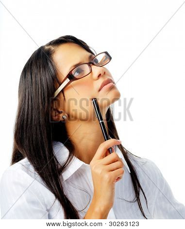 Young beautiful woman holding a pen against her face and looking up thinking