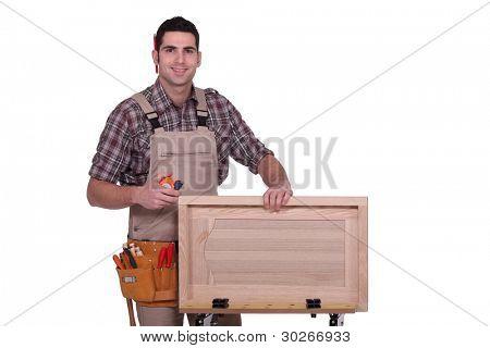 Man measuring cabinet door