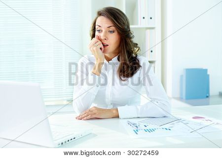 Concerned female office worker looking at the screen of laptop