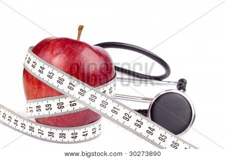 Fresh red apple wrapped with centimeter tape and stethoscope isolated on white