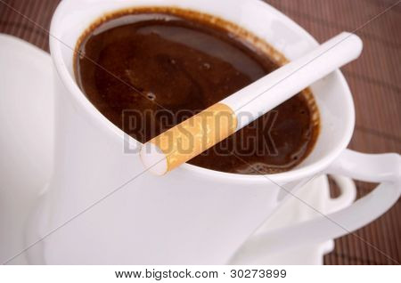 Whole cigarette on the full coffee cup